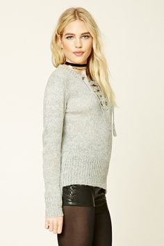 A marled knit sweater featuring a lace-up front with grommets, long sleeves, and ribbed trim.