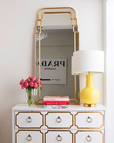 Feminine inspired vignette with a white and gold dresser, a gold mirror, a yellow lamp, and flowers