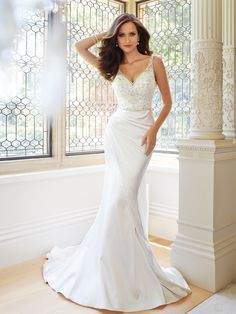 Sophia Tolli | Style No. › Y21447 | Wedding Dresses 2014 Collection – Opulence shines through in this beautifully cut shimmer satin sleeveless slim A-line gown. Luxurious embroidery and hand-beading adorn the V-neck bodice and semi-sheer plunging V-back neckline with crystal buttons. Jodie also features a side draped asymmetrical overlay skirt, concealed back zipper and a chapel length train. Sizes: 0 – 28
