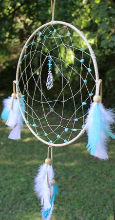 Turquoise Dreams This dream catcher is 12 inches with natural turquoise stone beading along with blue and white feathers and a silver and green feather pendant hanging in the center. Turquoise is a purification stone. It dispels negative energy and aligns all of the chakras.