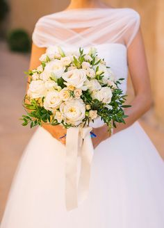 This beautiful bridal bouquet features fresh white roses and green leaves.