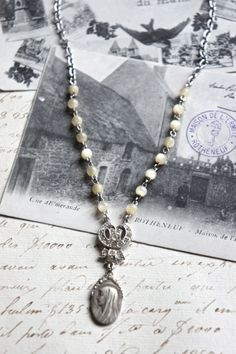 This beautiful necklace is adorned with a vintage religious of Mary surrounded in a wreath of tiny flowers. It is from Europe and has