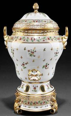 A Louis XVI~Paris porcelain~Polychrome and gilt decorated~Hot water urn~In three parts~Decorated with pansies and gilt floral sprays~Foliate loop handles Round pedestal base with foliate scroll feet~Origin France~Circa 177501800