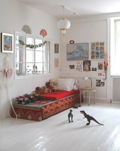 A boy's room with his  monsters on the floor and a Kilimcarpet on the bed