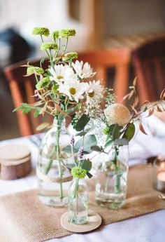 recycling old bottles and using wild flowers and a burlap runner, perfect for wedding in the country or barn or even your back yard. (personally i' like candles so you could add a couple votives to the mix and just a bit of babys breath, it perfect/comments walkingonsunshine:)