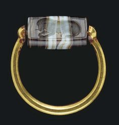 A GREEK GOLD AND BANDED AGATE FINGER RING  CLASSICAL PERIOD, CIRCA MID 5TH CENTURY B.C.  The heavy tapering hoop round in section, with disk terminals joined to a stout wire threaded through the perforation of the sliced barrel, engraved with a lioness