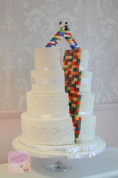 Elegant white wedding cake on the outside and lego on the inside! ! With lego 'bridging ' the gap and a lego bride and groom figures on top!