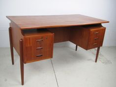 Beautiful teak desk with a floating top, sculpted teak drawer pulls and a very nice leg detail.