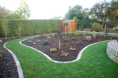 Grass paths defined with tegula block edges and low maintenance bark borders.