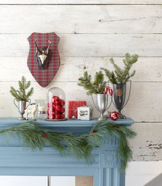 Give your mantel a rustic-preppy look with a resin reindeer ornament and plaid plaque. Antique trophys make cute vases for pine tree boughs. What's your holiday decorating style? »             - CountryLiving.com