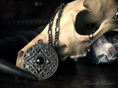 This ornately detailed silver pendant is fashioned after medieval shields and combining with it the beauty of nature. The pendant is an