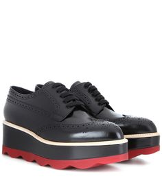 Prada - Leather platform brogues - Crafted from polished black leather with brogue detailing, these shoes from Prada come with a lofty platform that is sure to flatter your leg-line. The covetable pair are kept streamlined with an almond-shaped toe and layered grey and red sole. Team yours with a check sweater and miniskirt for a vintage-inspired look. seen @ www.mytheresa.com