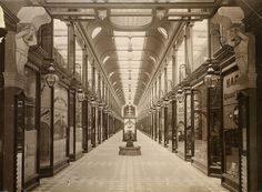 Adelaide Arcade, between Rundle & Grenfell Streets, 1886    B 2903    Photographer: Samuel White Sweet.    Captain Sweet also rented premises in the arcade. Looking south from Rundle Street. The arcade opened 12 December 1885. A pair of Atlantes figures support the ceiling and form a guard to the entrance. The architect's use of cast iron, plate glass and electric light made it a progressive building at the time, in fact it was one of Adelaide's first buildings to use electric lighting. The…