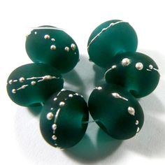 Transparent Dark Teal Green Handmade Lampwork Glass Beads 027 Shiny (Choices of Etched, .999 Fine Silver, Shapes, Sizes, Large Hole Beads Extra) These gorgeous beads are made using glossy transparent dark teal green glass. They are a rich deep blue green color. These handmade glass beads make elegant jewelry designs! They are beautiful beads that you can have in a shiny glass bead finish or go for the frosted handmade sea glass or beach glass look in an etched glass bead finish.