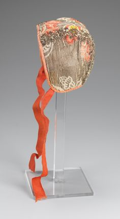 Child's cap, Norway, first half 18th century. Silk brocaded with large floral motifs in orange, salmon and white on light brown ground, decorated with metallic lace, orange silk ribbon binding.