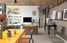 Living   As vigas de concreto ficaram aparentes já na primeira reforma. O assoalho de todo o apartamento é revestido com placas monolíticas, de 3,07 x 1,25 m, na cor cinza claro, da Formipiso (Foto: Edu Castello/Casa e Jardim)