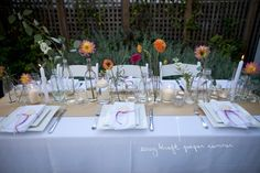 This is a simple, expensive table for a wedding. The runner is craft paper, the napkins are tied with yarn, and single flowers and greens are placed in various sized bottles. The effect is fun, casual, and chic, but inexpensive and easy to put together for a DIY wedding.