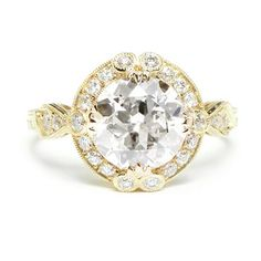 Boldly enchanting, this handcrafted ring features an Old European cut diamond in the center, which has facets resembling a blooming flower. ...