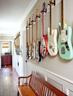 A musical twist to art on the wall ~ Songwriter Matthew Gerrard's guitar collection lines the wall on the way to his home office. - Home Decoz