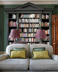 Green walls, and a contrasting dark green pedimented bookshelf,...