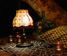 A solar-powered table lamp with orange patterned shade with fringes and a black base. Shown together with glass tealight holders with lit tealights and a colorful cushion.