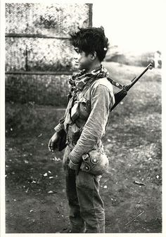 1966 South Vietnamese boy soldier with rifle strapped across his back.