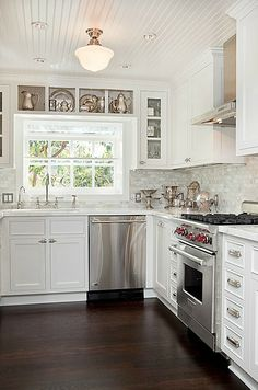 White kitchen with Beadboard Ceilings and carrera marble back splash
