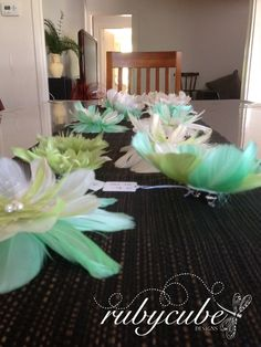 A table of mint, lettuce green & ivory feather flowers & fascinators for a wedding. Perfect for weddings, formal events or the races. Fascinators by Rubycube Designs.