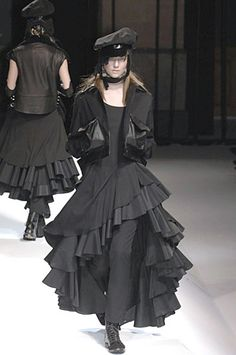 "Never conventionally sexy or trendy ""Mr. Yohji Yamamoto likes to dissolve sartorial boundaries"", Yamamoto appeals to clients who appreciate wit, romance, and fashion history. Although his palette is somber, he's never funereal; there's too much off-kilter joie de vivre in the floppy, flowing, sensual fabrics to bring down the mood. His menswear, launched in 1984, evinces the same gallery-friendly grandeur as his womenswear, apparent in the dark, textured jackets and voluminous trousers."