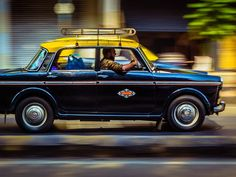 Technology-enabled taxis are helping fill a mobility service vacuum in Indian cities. Photo by Chrisbirds.com/Flickr. Dark blue-Yellow- a hint of burned orange and white.