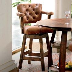 """Whether at the kitchen counter or a rec room bar you can belly-up in style with this tufted leather bar stool. The nailhead trim on the supple leather seat and arm rests and a sturdy wood frame give each stool a cushy feel and a classic look. 26""""W x 36""""D x 42""""H. Please allow 8-10 weeks for delivery. Made in USA."""