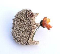 Crochet wire hedgehog holding a carnelian precious stone flower brooch