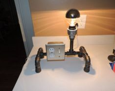 Black pipe table lamp with light switch and two plugs Desk Lamp, Table Lamp, Fighting Robots, Pipe Table, Black Pipe, Steampunk Lamp, Pipe Lamp, Light Project, Lightsaber