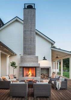 Stacked wood next to an outdoor fireplace with fantastic outdoor furniture. And I love the height on that chimney!