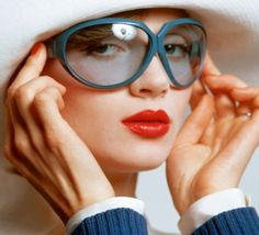 Model wearing blue tinted sunglasses and a white hat by Yves Saint Laurent, 1972