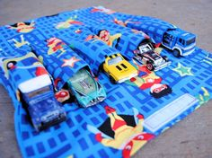 http://crazylittleprojects.com/2012/12/kids-car-carrier-tutorial.html  kid's car carrier. It holds 5 Hot Wheels or Matchbox cars and folds up easy so that it can be brought along when out and about. Supplies:  About 1/2 yard of kid friendly fabric  Thread  Cars to go in it