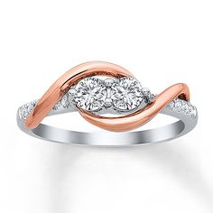 This two-stone anniversary ring for her shines with two round diamonds hugged in swirls of 14K rose gold. Additional round diamonds adorn the 14K white gold band. The ring has a total diamond weight of 1/2 carat. Diamond Total Carat Weight may range from .45 - .57 carats.