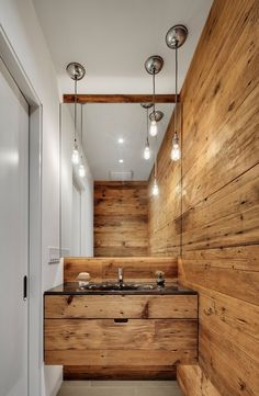 Rustic timber vanity and matching timber wall blends seamlessly to create balance. The horizontal grains on the vanity serve to run the viewers eye to the wall highlighting the height of the room and taking attention away from the bathrooms narrow space.