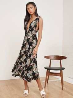 Treat yourself to something pretty. This is an ankle length dress with a fitted waist, knotted straps and a deep v neckline.