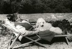Gertrude Stein relaxing at the Villa with Pepe sleeping at her neck, and her big standard poodle Basket between her legs.