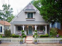 With+such+a+small+lot,+landscaping+takes+a+back+seat+to+improving+the+home's+architecture.+John+and+team+pull+out+all+the+stops+by+adding+layers+of+gingerbread-style+trim+that's+reminiscent+of+true+Victorian+architecture.+So+the+home's+main+color+doesn't+detract+from+the+trim+details,+the+team+paints+it+a+warm+neutral+tan+saving+the+cool+purples+and+blues+for+the+trim.+To+complete+the+fairytale+look,+a+picket+fence+lines+the+front+and+a+brick+path+leads+to+the+turquoise+front+door.