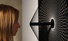 A Christie's employee in front of a Interference C by Jean-Pierre Yvaral at the kinetic art show. Photograph: Lefteris Pitarakis/AP