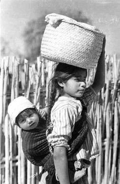 an old postcard photo taken in Oaxaca Mexico shows a girl carrying both a baby and a basket