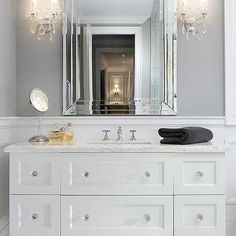 Two crystal sconces illuminate a white washstand with legs adorned with crystal knobs topped with white marble fitted with a white porcelain rectangular sink and polished nickel vintage cross handle faucet is tucked under a beveled mirror. White Master Bathroom, White Bathroom Cabinets, Master Bathrooms, White Cabinets, Art Deco Bathroom, Art Deco Mirror, Bathroom Ideas, Home Design, Crystal Sconce