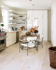 Designer Viki Mansell's kitchen offers a fresh take on the all-white kitchen with the light weathered wood lower cabinets, whitewashed floor and crisp white accents. A 3' x 6' reclaimed oak table with steel base adds dark contrast to the white space.
