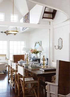 Nantucket dining room of Lee Bierly and Christopher Drake, New England home. The 11 foot long dining table is headed by antique Orkney chairs and lined with old fashioned bamboo director's chairs