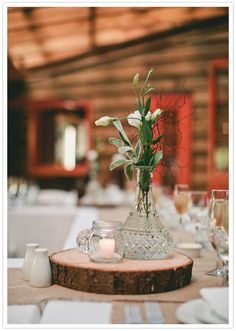 rustic wood log slice and simple, elegant crystal vase centerpiece with flowers | photo: www.baylymoore.com