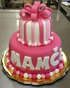 Dvoupatrový dort potažený růžovým fondánem s mašlí a fondánovými kuličkami.