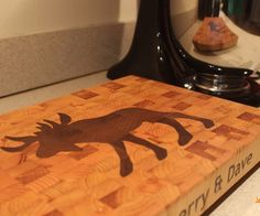 This is an end grain cutting board made from reclaimed white pine with inlay made from reclaimed mahogany. This pine comes from some salvaged paneling in a church renovation and the mahogany came from some old deck balusters. The cutting board features a moose as requested by a customer up in the great white north._______________Notable Materials:> Pine> Mahogany> Mineral Oil> Waterproof Wood Glue> Rubber Feet & Screws> Spray AdhesiveNotable T...