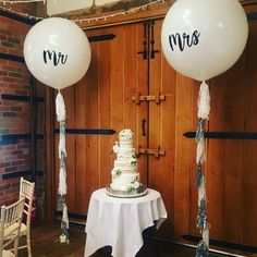 Mr and Mrs giant white balloons and silver and white tassel tails guard the cake at a wedding in the Dawley Barn at Lainston House, Hampshire Glitter Balloons, Bubble Balloons, Giant Balloons, White Balloons, Confetti Balloons, Bubbles, Glitter Dress, Wedding Balloons, Wedding Confetti